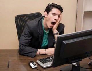 image homme qui baille devant un ordinateur lent